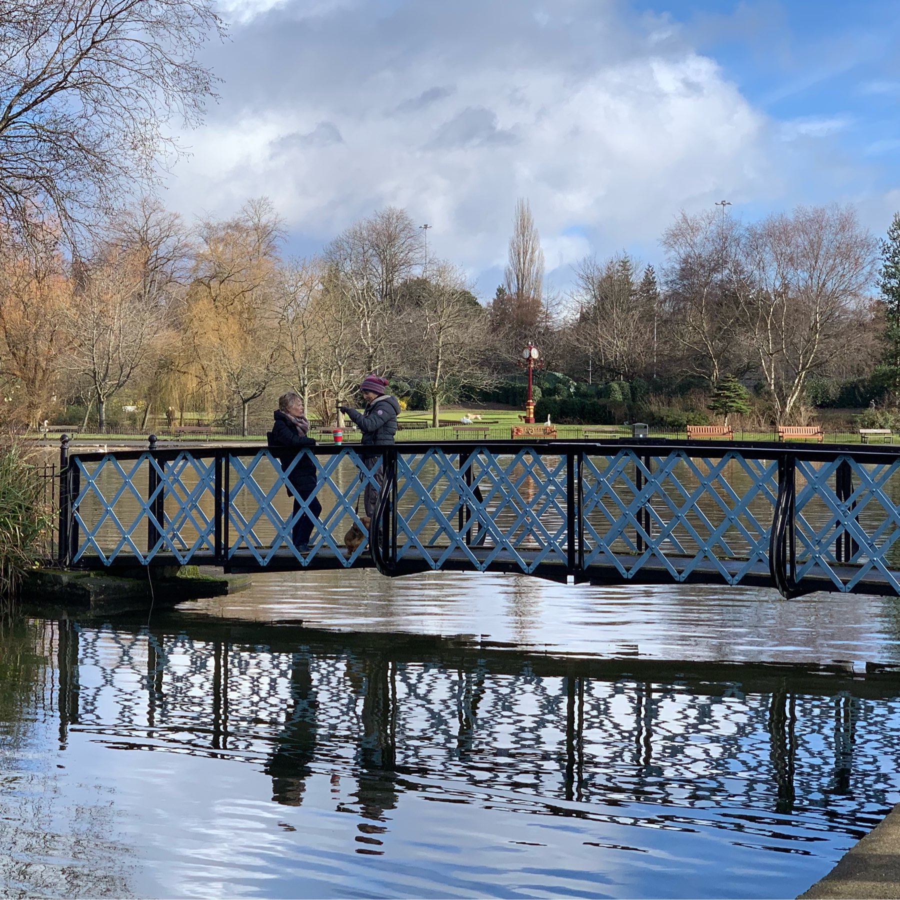 two people on bridge over pond
