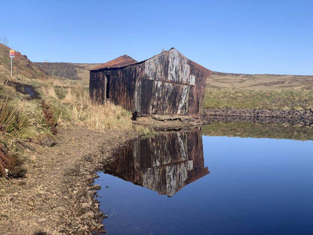 Corrugated iron hut reflected in loch